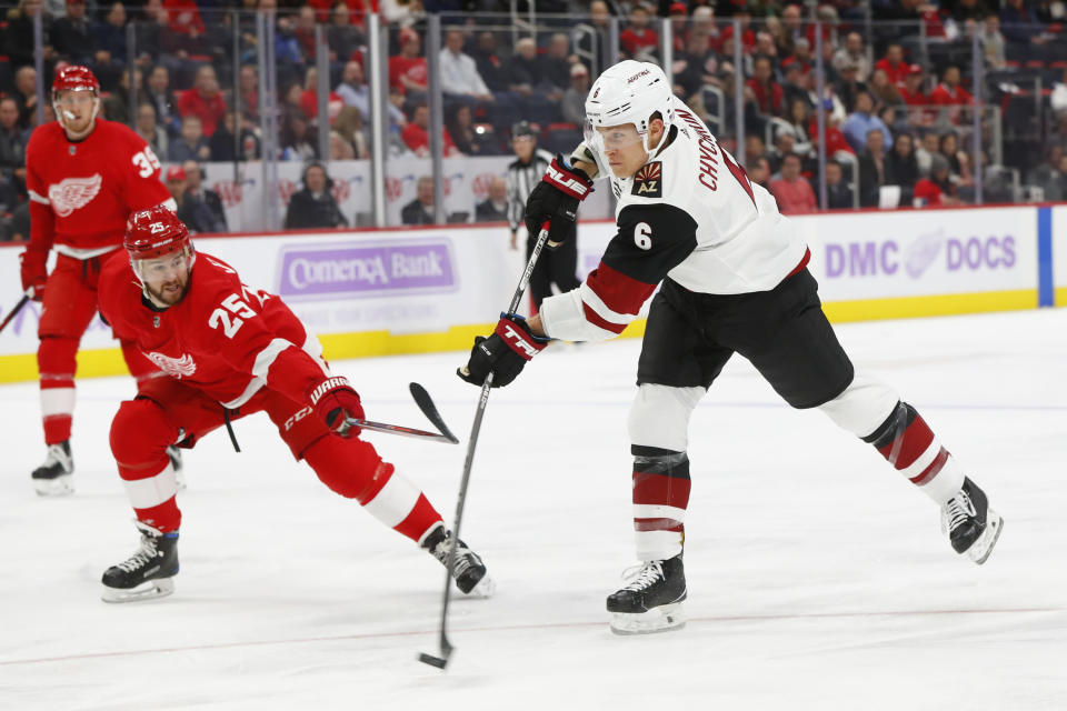 Arizona Coyotes defenseman Jakob Chychrun (6) shoots as Detroit Red Wings defenseman Mike Green (25) defends in the first period of an NHL hockey game Tuesday, Nov. 13, 2018, in Detroit. (AP Photo/Paul Sancya)