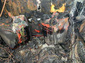 In this photo provided by Citrus County Fire Rescue melted gas cans sit amongst the charred remains of a Hummer that was destroyed by fire shortly after the driver had filled up four 5-gallon (18-liter) gas containers on Wednesday, May 12, 2021, in Homosassa, Fla. Many authorities are warning of the dangers of hoarding gas as shortages at the pumps are spreading from the South to the Mid-Atlantic states, following a cyberattack that forced a shutdown of the nation's largest gasoline pipeline. (Citrus County Fire Rescue via AP)