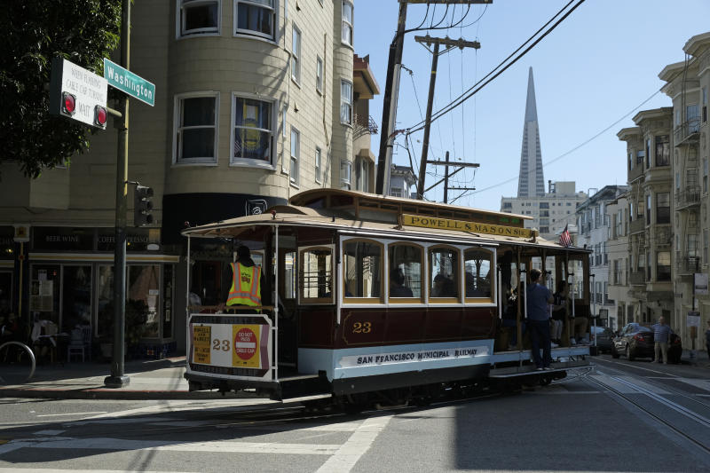 A cable car turns onto Washington Street with the Transamerica Pyramid in the background Wednesday, Sept. 11, 2019, in San Francisco. San Francisco's iconic cable cars will stop running for 10 days starting Friday to undergo repairs. The city's transit agency says it needs to get the manually operated cable cars off the street to rehabilitate the gearboxes that power the system that started in the 1890s. Shuttle buses will instead transport people along the steep streets of the cable car routes. (AP Photo/Eric Risberg)