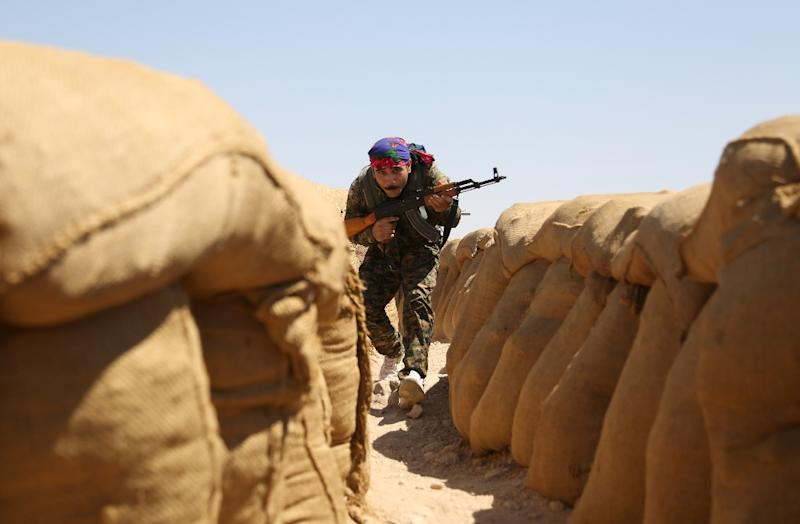 A Kurdish fighter guards a checkpoint near the northeastern Syrian city of Hasakeh