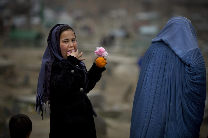 In this Friday, March 7, 2014 photo, an Afghan girl eats cotton candy as she visits with her mother a cemetery in the center of Kabul, Afghanistan. A gender and development specialist and human rights activist, Afghan Wazhma Frogh says her experience characterizes the women's rights movement in her country- after 12 years, billions of dollars and countless words emanating from the West commiserating with Afghan women, the successes are fragile, the changes superficial and vulnerable. (AP Photo/Anja Niedringhaus)
