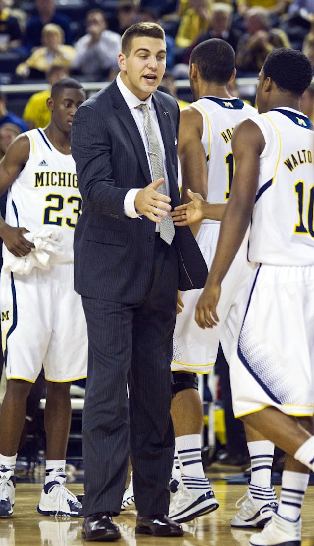 Michigan forward Mitch McGary, center, gives a hand to guard Derrick Walton Jr., right, during a timeout in the second half of an NCAA college basketball exhibition game with Wayne State, at Crisler Center in Ann Arbor, Mich., Monday, Nov. 4, 2013. Michigan won 79-60. (AP Photo/Tony Ding)