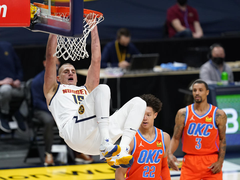 Denver Nuggets center Nikola Jokic, left, hangs from the rim after dunking the ball for a basket against Oklahoma City Thunder forward Isaiah Roby, center, and guard George Hill in the first half of an NBA basketball game Tuesday, Jan. 19, 2021, in Denver. (AP Photo/David Zalubowski)