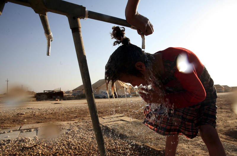 In this Thursday Aug. 2, 2012 photo a Syrian refugee girl washes up and cools off in Zaatari Refugee camp, in Mafraq, Jordan. Jordan is host to the largest number of Syrian refugees at 142,000, including hundreds of army and police defectors and leaders in the rebel Free Syrian Army, fighting in the civil war that erupted in March 2011. (AP photo/Mohammad Hannon)