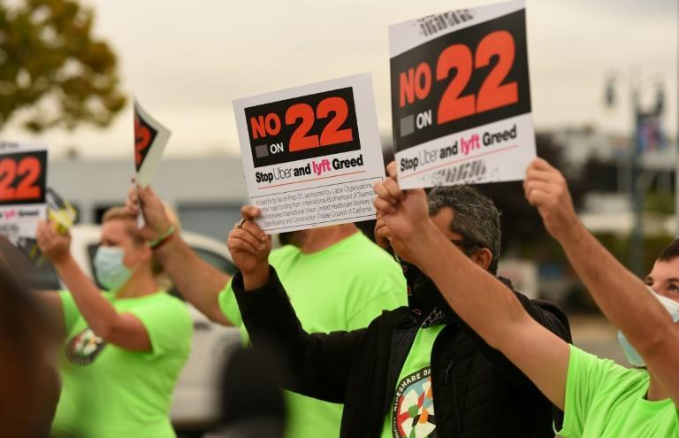 """Rideshare drivers hold signs supporting a """"No"""" vote on Proposition 22 in Oakland, California on October 09, 2020"""