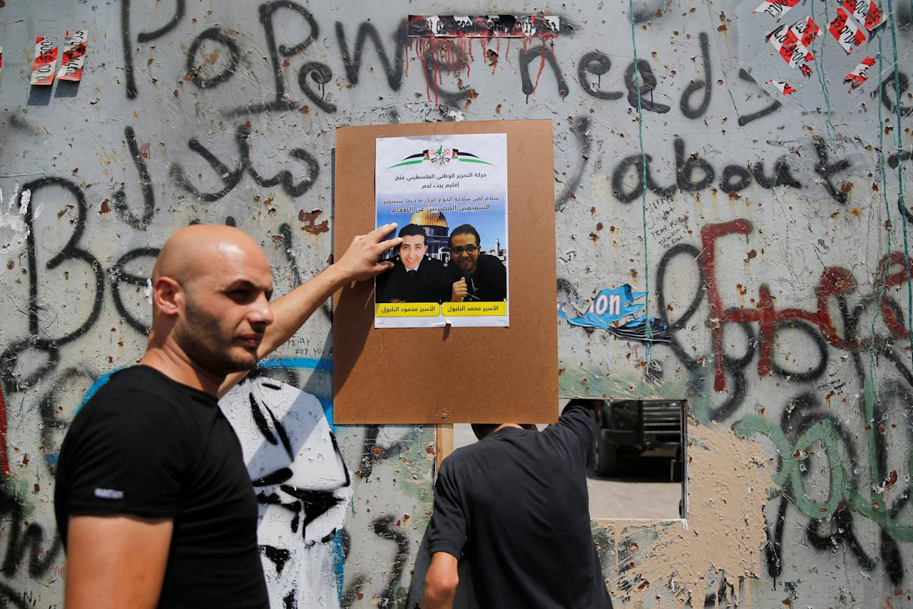 A demonstrator touches a poster featuring an image of two jailed Palestinian brothers during a rally in support of Palestinian prisoners held in Israeli jails, in the West Bank town of Bethlehem September 5, 2016. REUTERS/Ammar Awad
