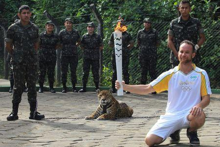 Brazilian physiotherapist Igor Simoes Andrade poses for picture next to jaguar Juma as he takes part in the Olympic Flame torch relay in Manaus, Brazil, June 20, 2016. Picture taken June 20, 2016. REUTERS/Marcio Melo