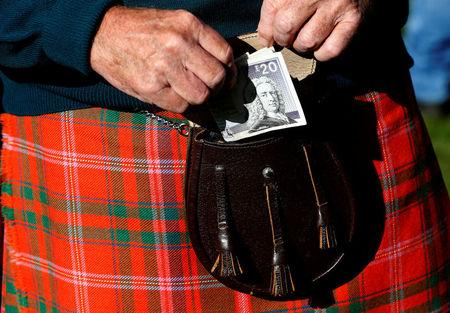 FILE PHOTO: A man puts money in his sporran at the Birnam Highland Games in Scotland, Britain August 30, 2014. Scotland will hold a referendum on independence on September 18. REUTERS/Russell Cheyne/File Photo