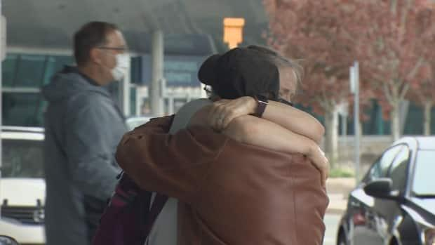 Brian Meaney and Laura Muranyi, father and daughter, embrace after months apart due to COVID-19. It was one of many such scenes at the airport this week. (Curtis Hicks/CBC - image credit)
