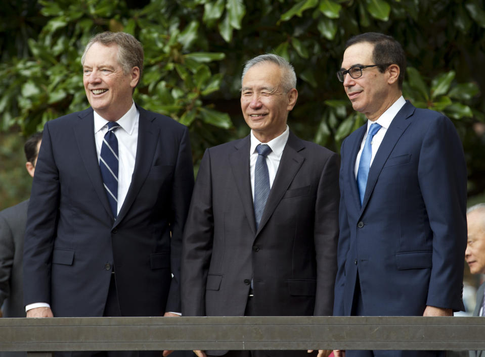 FILE - In this Oct. 10, 2019, file photo Chinese Vice Premier Liu He accompanied by U.S. Trade Representative Robert Lighthizer, left, and Treasury Secretary Steven Mnuchin, greets the media before a minister-level trade meetings at the Office of the United States Trade Representative in Washington. US and China are trying to finalize a modest trade agreement to deescalate a trade war that has rattled financial markets and hobbled global economic growth. (AP Photo/Jose Luis Magana, File)