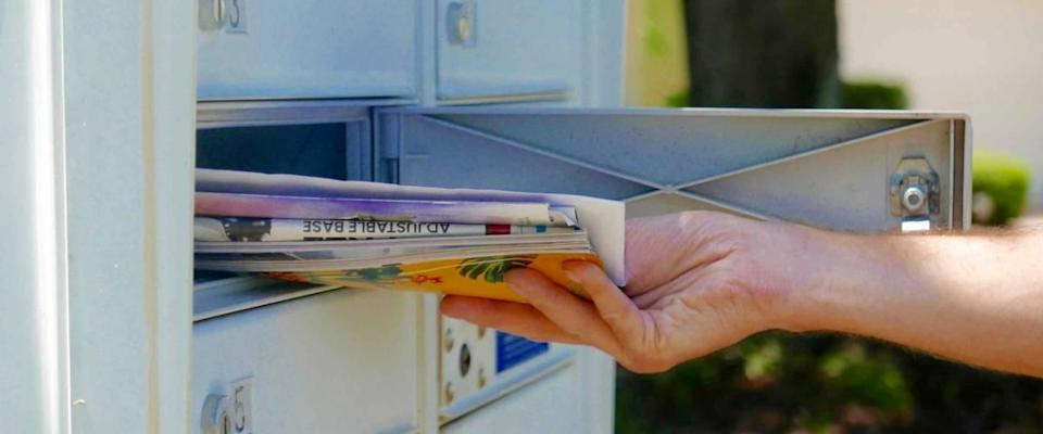 Person's hand pulling a pile of mail out of an outdoor community mailbox