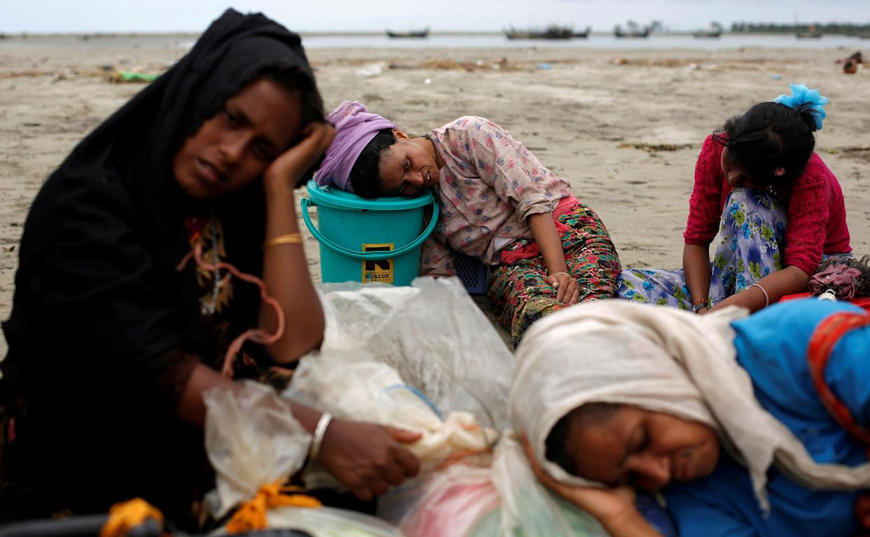 Exhausted Rohingya refugees rest on the shore after crossing the Bangladesh-Myanmar border by boat through the Bay of Bengal in Shah Porir Dwip, Bangladesh, on Sept. 10, 2017.