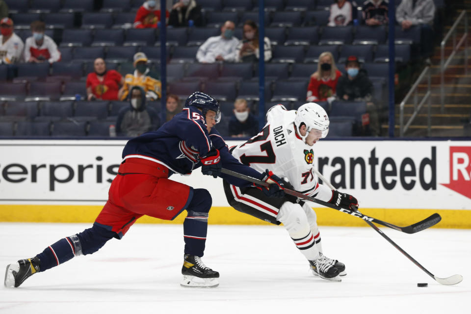 Chicago Blackhawks' Kirby Dach, right, looks for an open shot as Columbus Blue Jackets' Gabriel Carlsson defends during the first period of an NHL hockey game Saturday, April 10, 2021, in Columbus, Ohio. (AP Photo/Jay LaPrete)