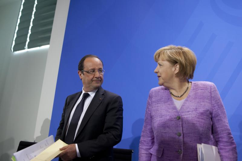 """German Chancellor Angela Merkel and French President Francois Hollande attend a press conference after the """"Conference on Promoting Youth Employment in Europe"""" in Berlin, Germany, Wednesday, July 3, 2013. (AP Photo/Axel Schmidt)"""