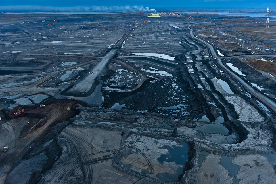 As twilight falls on the Alberta tar sands, the stripped landscape takes on an oily blue tint.