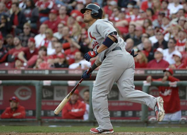 St. Louis Cardinals' Yadier Molina hits a solo home run off Cincinnati Reds starting pitcher Johnny Cueto in the seventh inning of a baseball game, Monday, March 31, 2014, on opening day in Cincinnati. (AP Photo/Michael Keating)