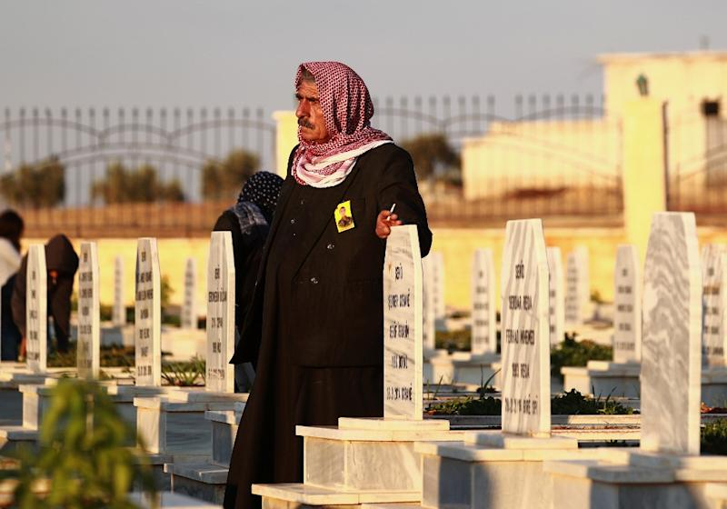 A man in the northern Syrian town of Kobane walks in a graveyard during the funeral of a fighter of the Syrian Democratic Forces killed in an offensive by the Islamic State movement (AFP Photo/Delil SOULEIMAN)