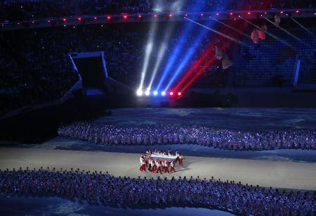 Russian athletes carry their national flag into the stadium during the closing ceremony for the 2014 Sochi Winter Olympics, February 23, 2014. REUTERS/Eric Gaillard