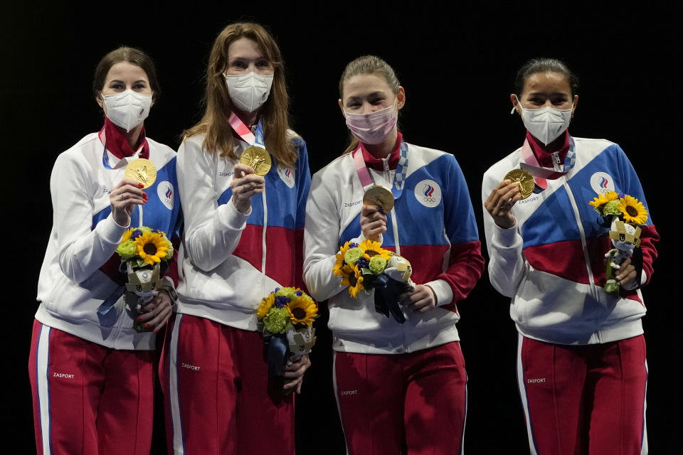 Gold medalists from the Russian Olympic committee celebrate on the podium of the women's Foil team final at the 2020 Summer Olympics, Thursday, July 29, 2021, in Chiba, Japan. (AP Photo/Hassan Ammar)