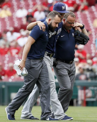 Milwaukee Brewers relief pitcher Dan Jennings is helped off the field after an injury in the eighth inning of a baseball game against the Cincinnati Reds, Thursday, Aug. 30, 2018, in Cincinnati. (AP Photo/John Minchillo)
