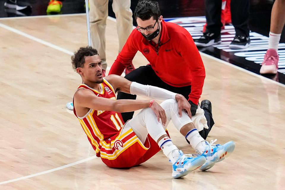 Trae Young is attended to after injuring his ankle by accidentally stepping on an official's foot during Game 3.