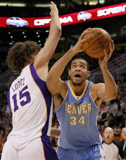 Denver Nuggets' JaVale McGee (34) slips past Phoenix Suns' Robin Lopez during the first half of an NBA basketball game on Saturday, April 21, 2012, in Phoenix. (AP Photo/Matt York)