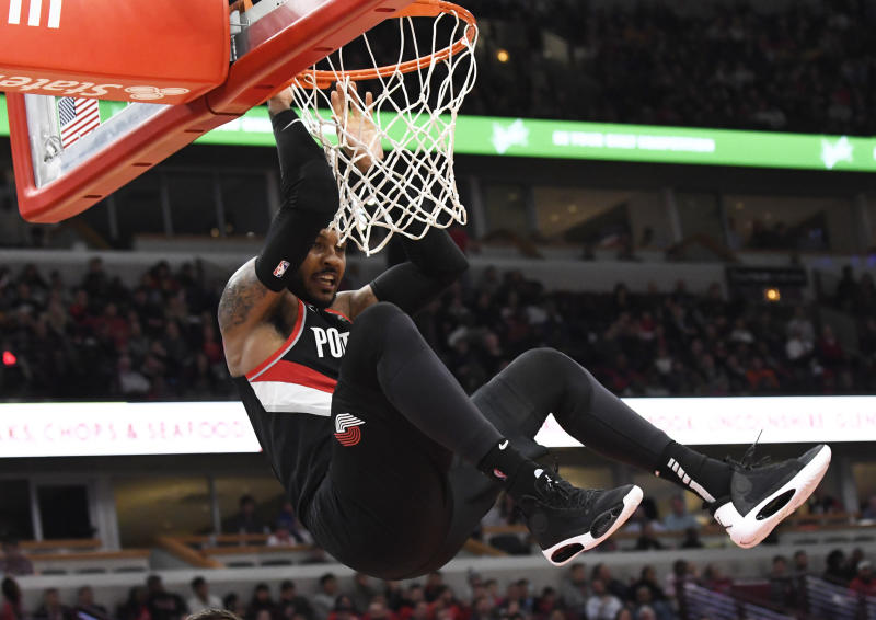 Nov 25, 2019; Chicago, IL, USA; Portland Trail Blazers forward Carmelo Anthony (00) hangs on the rim after dunking the ball against the Chicago Bulls during the second half at United Center. Mandatory Credit: David Banks-USA TODAY Sports