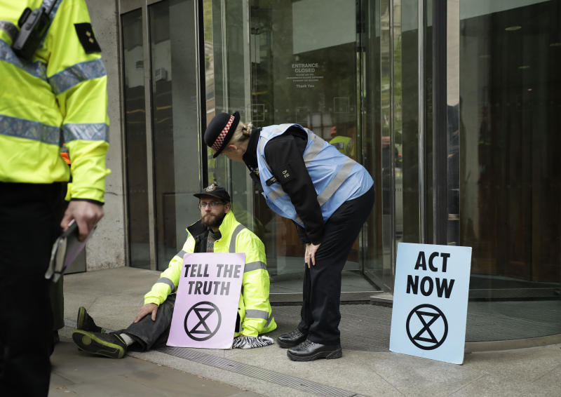 An Extinction Rebellion climate change protester with his hand glued to the floor outside the London Stock Exchange talks to a police officer in the City of London, Thursday, April 25, 2019. The non-violent protest group, Extinction Rebellion, is seeking negotiations with the government on its demand to make slowing climate change a top priority. (AP Photo/Matt Dunham)