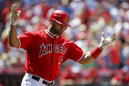 Los Angeles Angels' Albert Pujols reacts after flying out with the bases loaded against the Texas Rangers to end the seventh inning of a baseball game in Anaheim, Calif., Sunday, June 3, 2012. (AP Photo/Chris Carlson)
