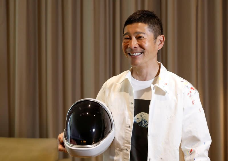 Japanese billionaire Yusaku Maezawa poses with a space suit helmet during the interview with Reuters in Tokyo