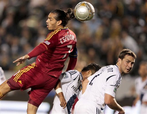 Real Salt Lake forward Fabian Espindola, left, attempts a header over Los Angeles Galaxy defender Todd Dunivant, right, and defender A.J. DeLaGarza, middle, during the first half of an MLS soccer match, Saturday, March 10, 2012, in Carson, Calif. Real Salt Lake won 3-1. (AP Photo/Bret Hartman)