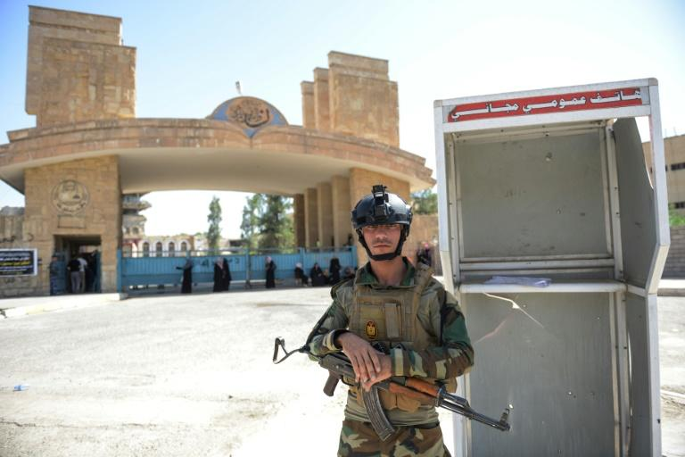 An Iraqi soldier stands guard outside the University of Mosul as students arrive to take their exams