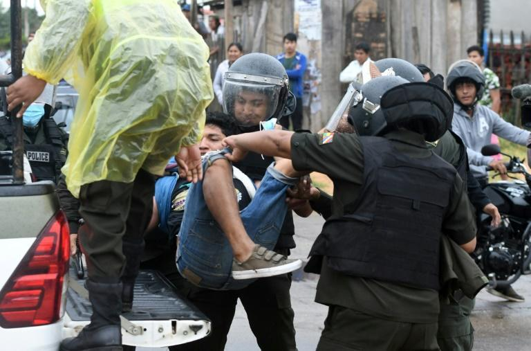 Riot police detain a man during a demonstration against the Bolivian government in Santa Cruz, on October 11, 2021. (AFP/Rodrigo URZAGASTI)