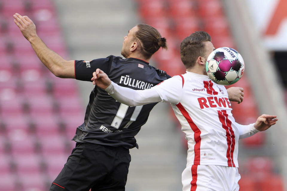 Bremen's Niclas Fuellkrug, left, and Cologne's Jannes Horn, right, challenge for the ball during the German Bundesliga soccer match between 1. FC Cologne and Werder Bremen in Cologne, Germany, Sunday, March 7, 2021. (Rolf Vennenbernd/dpa via AP)