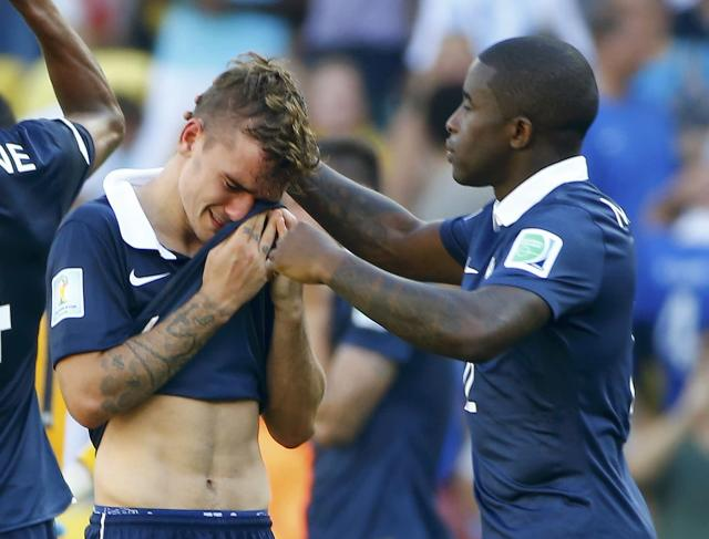 France's Rio Mavuba (R) consoles his teammate Antoine Griezmann after losing their 2014 World Cup quarter-finals soccer match against Germany at the Maracana stadium in Rio de Janeiro July 4, 2014. REUTERS/Pilar Olivares (BRAZIL - Tags: SOCCER SPORT WORLD CUP)