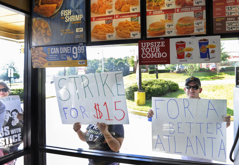 David Atten, right, joins others in demonstrating as he presses a sign to the window of a Church's Chicken during a one-day strike coinciding with strikes at other fast food restaurants across the country, Thursday, Aug. 29, 2013, in Atlanta. Workers are demanding $15 an hour and the right to form a union without interference from employers. (AP Photo/John Amis)