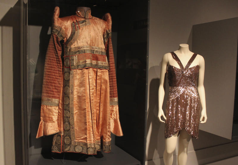 """In this Thursday, Sept. 13, 2012 photo, a brocaded Mongolian silk tunic called a """"deel"""" at left is seen next to a sequined chiffon shoulderless cocktail dress from the 2008 fall collection by fashion designer Maria Pinto in the new exhibit """"Fashion and The Field Museum Collection: Maria Pinto"""" opening Friday, Sept. 14 at the museum in Chicago. The exhibit features Maria Pinto designs alongside antiquities from the museum. (AP Photo/Caryn Rousseau)"""