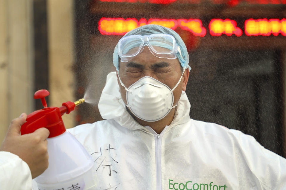 FILE - In this Feb. 3, 2020,file photo, a worker in a protective suit is disinfected outside a hotel being used for people held in medical isolation in Wuhan in central China's Hubei province. The Chinese city of Wuhan is looking back on a year since it was placed under a 76-day lockdown beginning Jan. 23, 2020. (Chinatopix via AP, File)