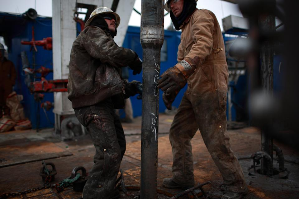FORT WORTH, TX - DECEMBER 16: Floor hands tighten 30-foot sections of steel pipe at a natural gas well site on December 16, 2008 in Fort Worth, Texas. Drilled in a residential area with mineral rights leased from a local owner, the 11,000' well is owned by Chesapeake Energy Corporation. Urban wells are required to be 600 feet from the nearest homes, schools, churches, hospitals and parks. Multiple wells on a site require less distance. In Texas, state law gives owners of mineral rights the prerogative over owners of surface land. One of the largest natural gas fields in the US, the Barnett Shale formation, discovered in the early 1950's, covers 5,000 square miles underlying the Dallas-Fort Worth area and is proven to hold 2.5 trillion cubic feet of natural gas. The Barnett Shale is known as a tight gas reservoir in hard shale rock and requires hydraulic fracturing technology to properly release the underground gas. Drilling in urban areas of Fort Worth has been a contentious issue between city councils, local residents, large land holders and influential energy companies. Residents have been objecting to heavy truck traffic of 18-wheel service vehicles, road destruction, noise, dust and waste water removal. Fort Worth has been called the guinea pig for natural gas drilling in close proximity to residential areas. (Photo by Robert Nickelsberg/Getty Images)