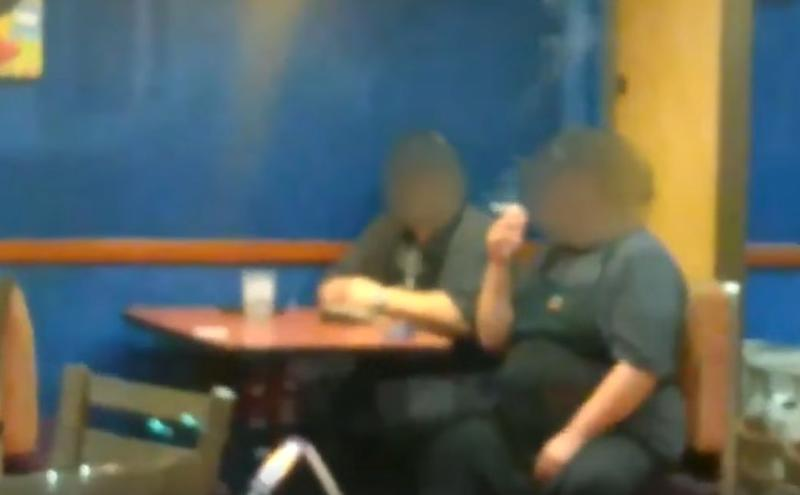 Two Taco Bell employees in North Carolina were captured on video smoking inside an empty store, despite a long line at the drive-thru. (Photo: Facebook)