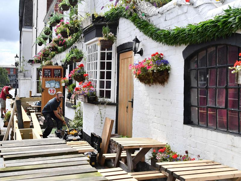 """Workers prepare an outdoor seating area at a pub in Birmingham on 2 July, 2020, ahead of """"super Saturday"""": JUSTIN TALLIS/AFP via Getty Images)"""