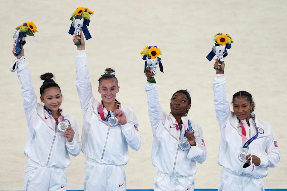 Simone Biles and Team USA pose with their silver medals from the team all-around competition.