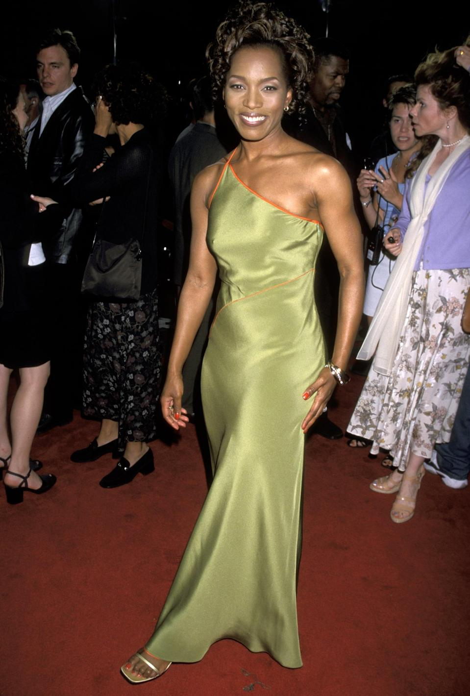 <p>Angela Bassett looked divine in this satin green one-shoulder dress at the <strong>How Stella Got Her Groove Back </strong>premiere in 1998. The thin orange accents added a pop of contrast, and she finished the outfit with effortless strappy sandals. </p>