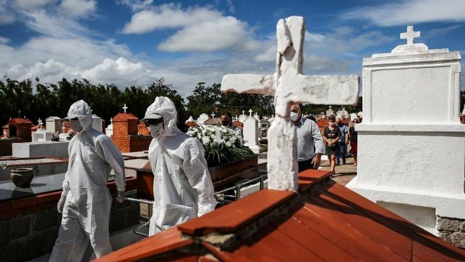 Workers wearing protective gear pull the coffin during the burial of Lucio Pereira de Lima, 61, who passed away due to the coronavirus disease (COVID-19), at Belem Novo cemetery in Porto Alegre, Brazil April 2, 2021.