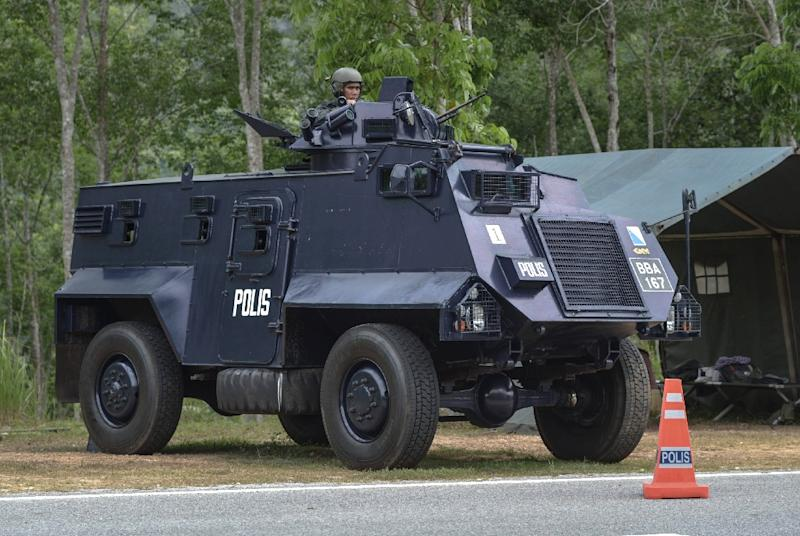 A Malaysian policeman mans an armoured vehicle at a security checkpoint in Wang Kelian near the Malaysia-Thailand border, on May 25, 2015 (AFP Photo/Mohd Rasfan)