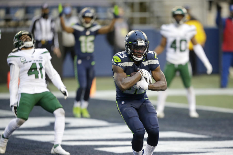 Seattle Seahawks wide receiver David Moore cradles the ball after catching a touchdown pass as New York Jets safety Matthias Farley (41) reacts behind during the second half of an NFL football game, Sunday, Dec. 13, 2020, in Seattle. (AP Photo/Lindsey Wasson)