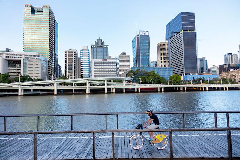 A man rides bicycle on the boardwalk on South Bank in Brisbane.