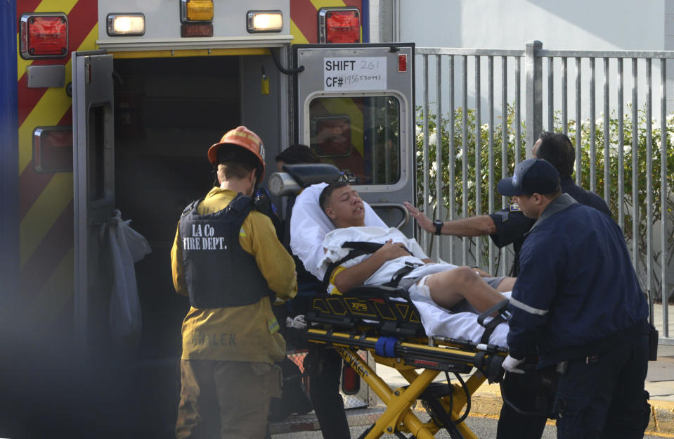 Medical personnel load an injured person into an ambulance outside Saugus High School in Santa Clarita, Calif., after a student gunman opened fire at the school on Thursday, Nov. 14, 2015. (Rick McClure via AP)