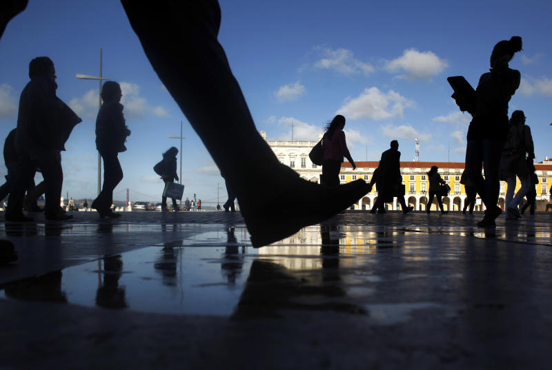 Commuters walk along Comercio square during a 24-hour subway workers strike, Lisbon, Thursday, May 30, 2013. The strike snarled rush-hour traffic in the Portuguese capital in the latest protest against the bailed-out country's austerity policies. Unions representing subway workers called the walkout Thursday over labor reforms and cuts in entitlements. The government is enacting those measures in return for a euro 78 billion ($101 billion) financial rescue two years ago. (AP Photo/Francisco Seco)