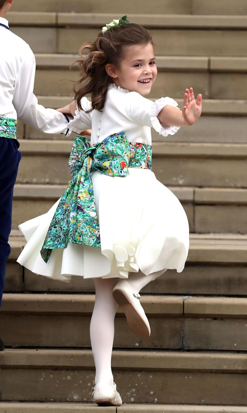 A bridesmaid gives a wave to the crowds.